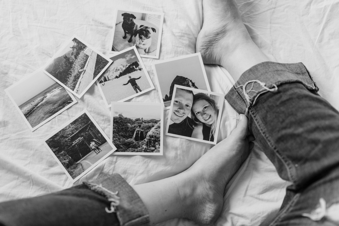 Photographs of past memories displayed on a woman's bed.