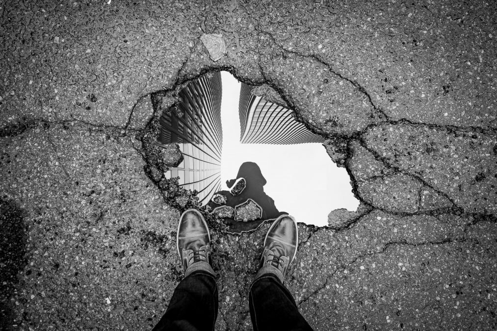 Man looking at his reflection in a puddle.